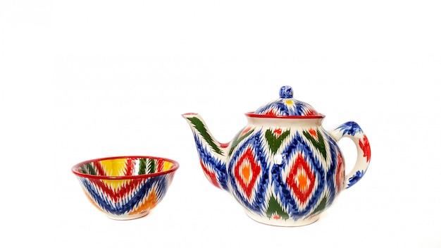 Utensili tradizionali dell'uzbeco - bollitore, ciotola con ornamento ikat su bianco, isolato