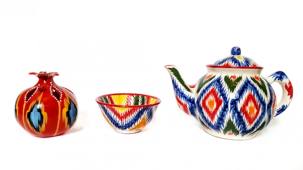 Utensili tradizionali uzbeko - bollitore, ciotola, melograno con ornamento ikat su bianco, isolato