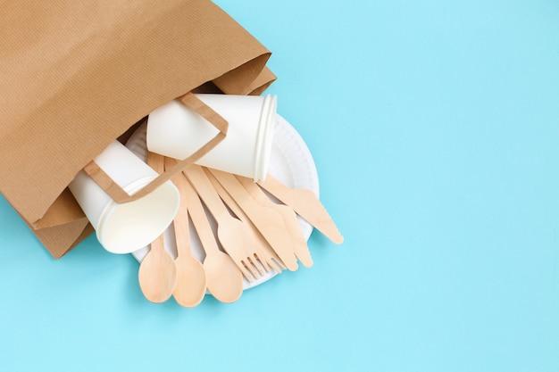 Utensili usa e getta ecologici fatti di legno di bambù in un sacchetto di carta sul blu.