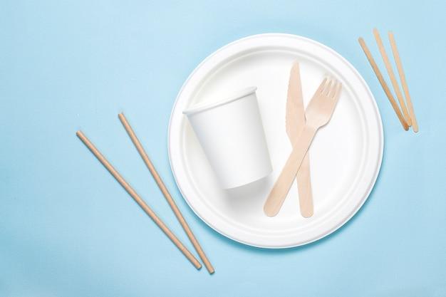 Utensili usa e getta ecologici in legno di bambù e carta su sfondo blu. cucchiai, forchette, coltelli, ciotole di bambù con bicchieri di carta.