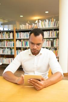 Utente maschio serio che utilizza la connessione internet wireless