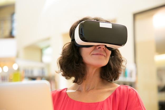 Utente soddisfatto del dispositivo femminile che gode dell'esperienza di realtà virtuale