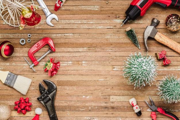 Utili strumenti di costruzione con ornamenti natalizi su legno