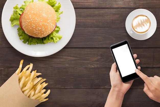 Utilizzando smartphone con hamburger, patatine fritte e set da caffè sullo sfondo in legno. copyspace per il tuo testo