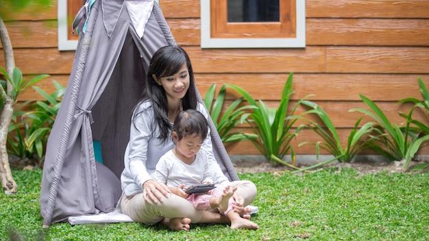 Utilizzando tablet mentre si gioca nel cortile di casa