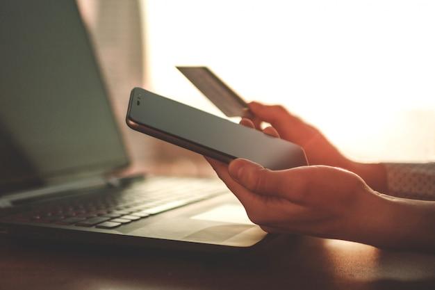 Utilizzando un computer portatile, una carta di credito e un telefono cellulare per acquistare e pagare beni.