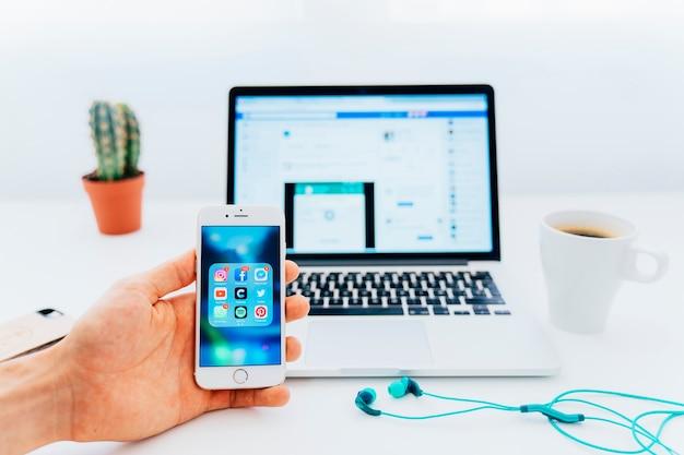 Utilizzo di applicazioni sul telefono e facebook sul computer portatile