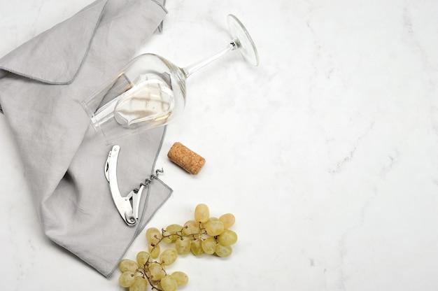 Uva, cavatappi, tappo per vino e bicchiere con vino bianco