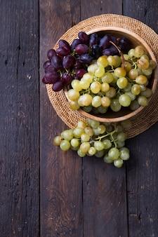 Uva da vino rossa e bianca di frutti sani su superficie di legno s