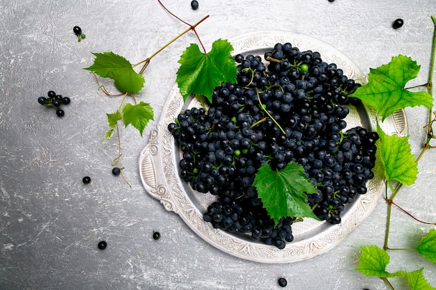 Uva da vino rosso in vassoio d'argento su superficie grigia,