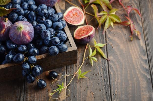 Uva e fichi neri freschi in vassoio di legno scuro sulla tavola di legno