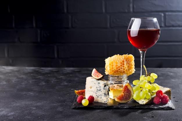Uva, formaggio, fichi e miele con un bicchiere di rosso su una pietra nera sfondo, copia spazio