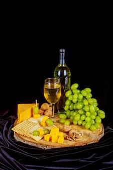 Uva, formaggio, fichi e miele con un bicchiere di vino bianco su uno sfondo di legno.