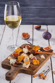 Uva, formaggio, fichi e miele con un bicchiere di vino rosso e bianco su una tavola di legno