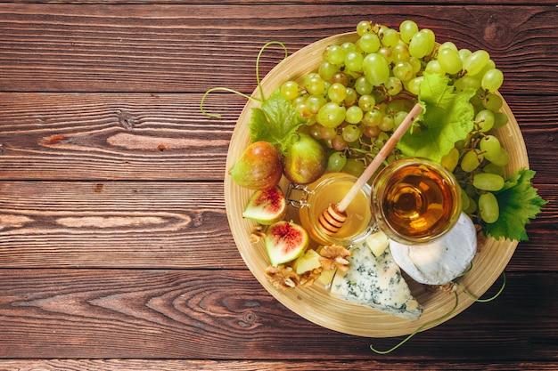 Uva, formaggio, fichi e miele con vino sul tavolo di legno