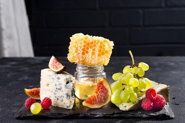 Uva, formaggio, fichi e miele su una pietra nera su sfondo nero muro di mattoni, copia spazio