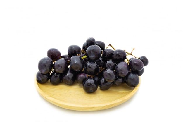 Uva fresca sul piatto di legno isolato su sfondo bianco