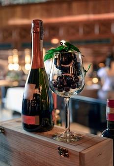 Uva in bicchiere di vino con bottiglia di champagne sulla scatola di legno