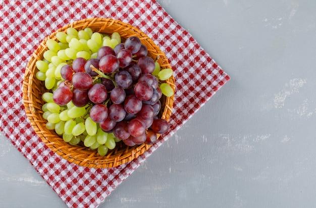 Uva in un cesto di vimini su stoffa da picnic e intonaco,