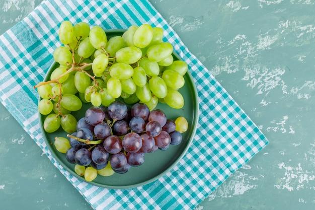 Uva in un vassoio su intonaco e sfondo di stoffa da picnic. laici piatta.