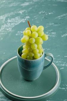Uva in una vista di alto angolo della tazza sul fondo del vassoio e dell'intonaco