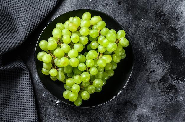 Uva matura verde in un piatto, frutti dell'autunno. sfondo nero.