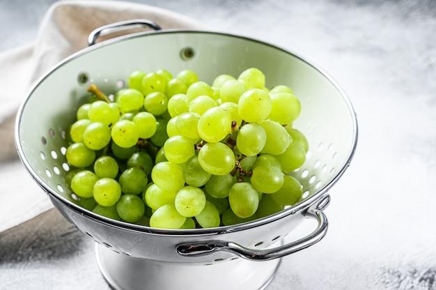 Uva matura verde in uno scolapasta, frutti dell'autunno. sfondo bianco. .