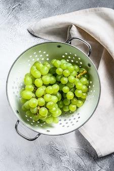 Uva matura verde in uno scolapasta, frutti dell'autunno. sfondo bianco.