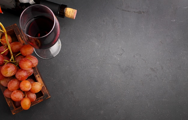 Uva matura, vino rosso e un bicchiere su uno sfondo nero