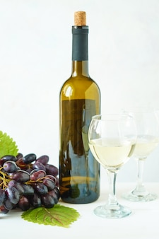 Uva nera con un bicchiere di vino bianco e una bottiglia di vino su un tavolo luminoso