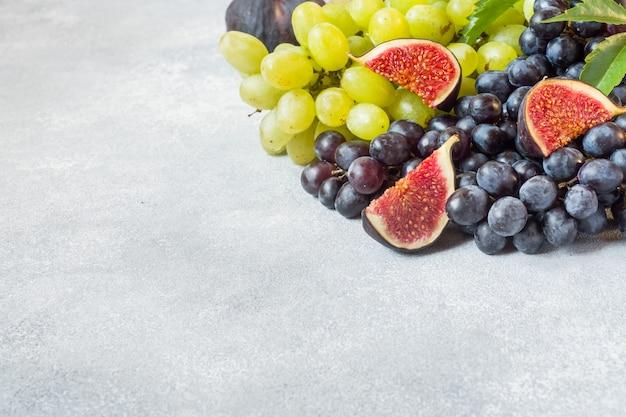 Uva nera e verde, fichi e foglie su un tavolo grigio
