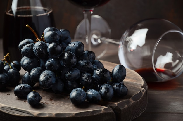 Uva nera fresca e vino rosso sulla tavola di legno