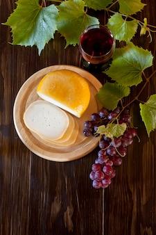 Uva rossa con foglie, bicchiere di vino e formaggio fresco su legno rustico. vista dall'alto, primo piano.