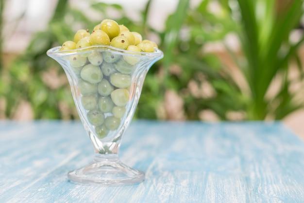 Uva spina congelate delle bacche in una ciotola di vetro sulla tavola d'annata.