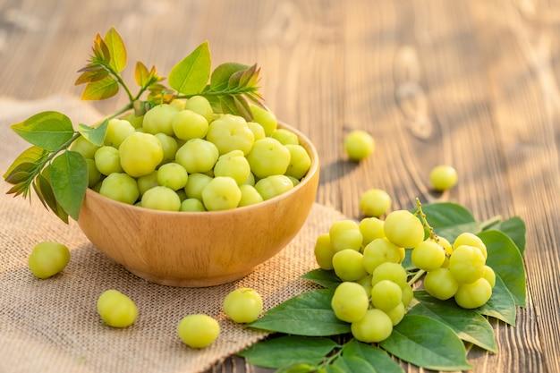 Uva spina verde fresca della stella (frutta tailandese tropicale) in ciotola sulla plancia di legno