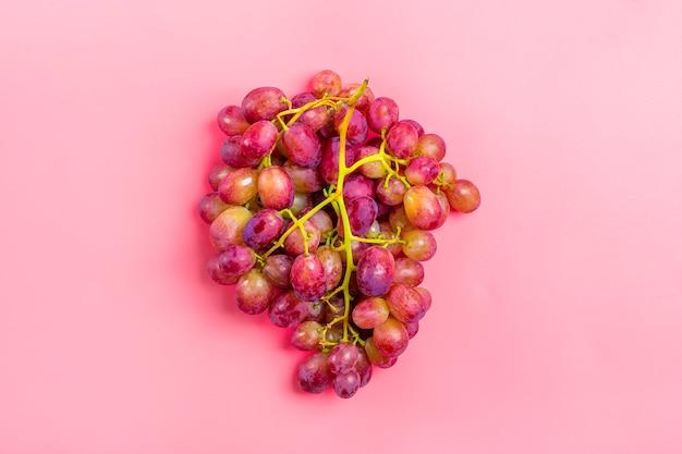 Uva succosa nera organica naturale sulla superficie rosa di tendenza vista superiore vista piana