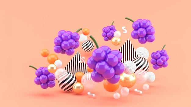 Uva tra le palline colorate sullo spazio rosa