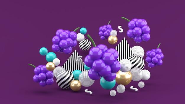 Uva tra le palline colorate sullo spazio viola