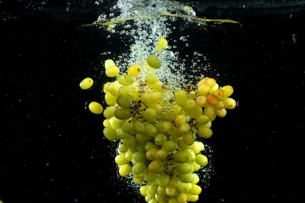 Uva verde che spruzza nell'acqua nel nero