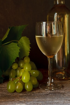 Uva verde con foglie, vetro, bottiglia di vino bianco