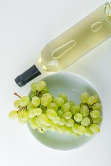 Uva verde con vino in un piatto su bianco,