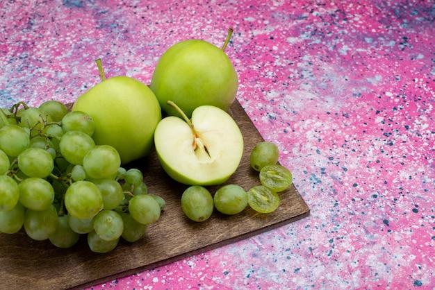 Uva verde di vista vicina della parte anteriore insieme alla mela verde sullo scrittorio viola