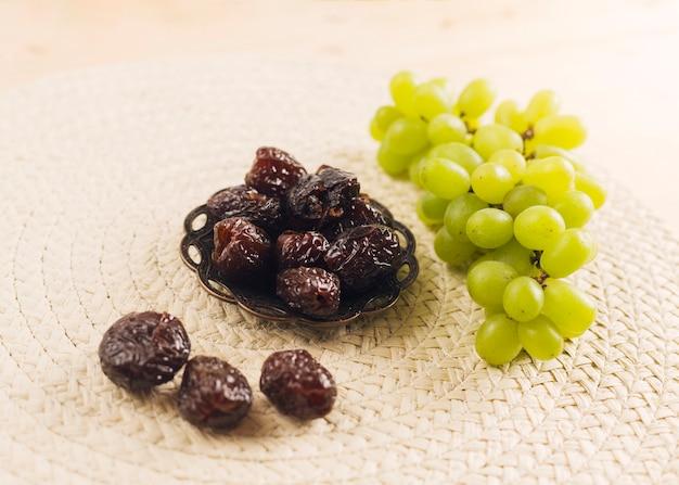 Uva verde fresca vicino prugne sul piattino