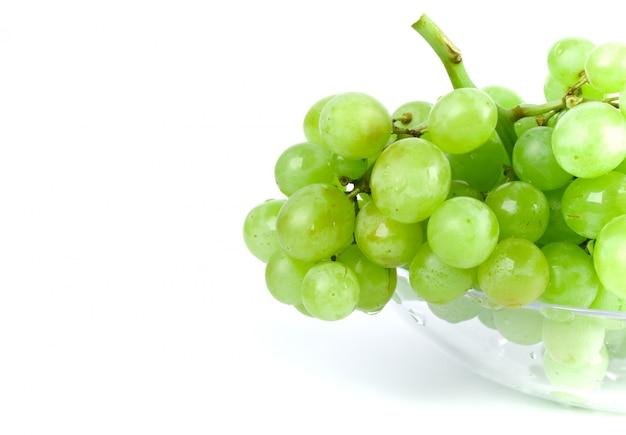 Uva verde in ciotola su sfondo bianco