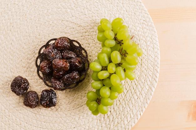 Uva verde vicino prugne sul piattino