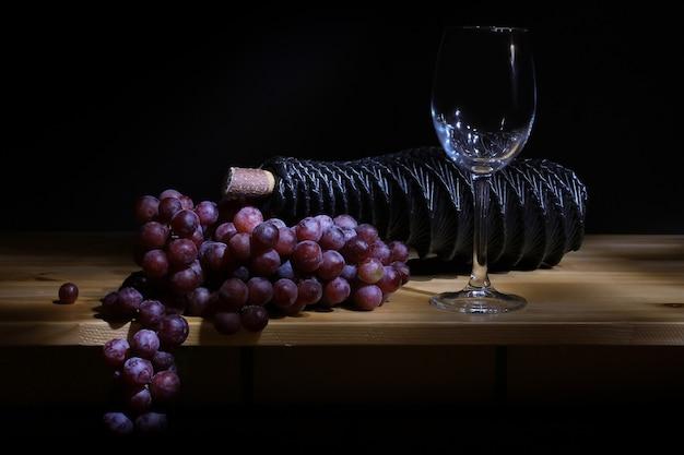 Uve fresche e una bottiglia di vino con un bicchiere