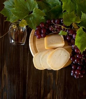 Uve rosse con foglie, bicchiere di vino e formaggio fresco. vista dall'alto, primo piano.