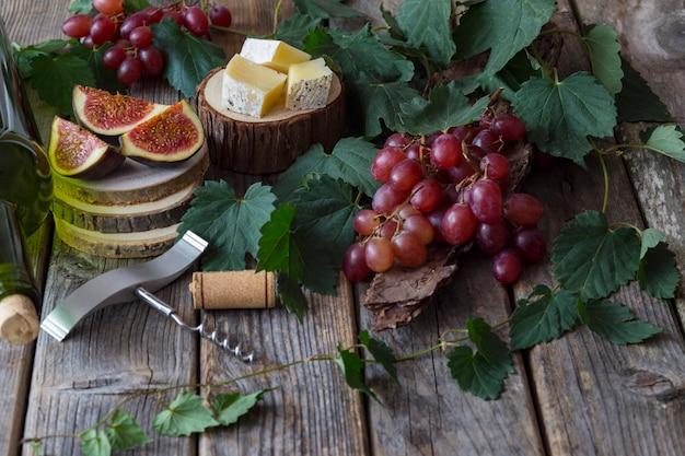 Uve rosse, una bottiglia di vino, un bicchiere, fichi e formaggio su un supporto di legno, una bottiglia di vino