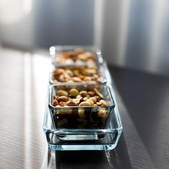 Uvetta, arachidi e pistacchio in eleganti ciotole di vetro