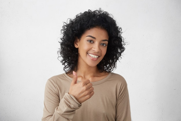 Va molto meglio. bella giovane donna entusiasta allegra della corsa mista con capelli ricci che mostrano i pollici sul gesto